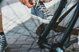 Unrecognizable young man ties up shoelaces on sneakers before a bike ride against the backdrop of a bicycle wheel