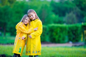 Cute toddler girls wearing waterproof coat playing outdoors by rainy and sunny day