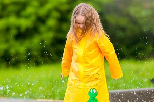 Little girl in raincoat and boots playing in the rain outdoors