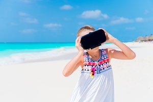 Little girl using VR virtual reality goggles. Adorable kid look into the virtual glasses on white beach