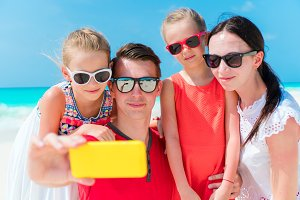 Young family taking selfie portrait on the beach
