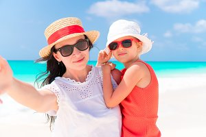 Mother and little kid taking selfie at tropical beach