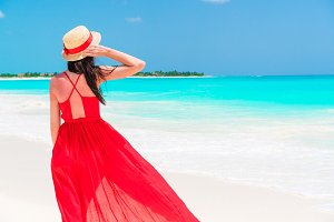 Beautiful woman on tropical seashore. Young girl in beautiful red dress background the sea