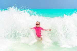 Adorable little girl at beach having a lot of fun in water