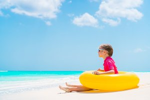 Adorable little girl with inflatable rubber circle have fun on the beach
