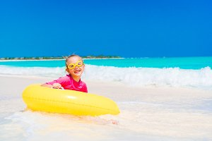 Adorable little girl with inflatable rubber circle splashing. Kid having fun on summer active vacation