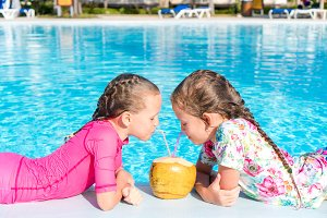 Kids in outdoor swimming pool drink coconut milk