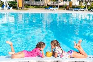 Little girls in outdoor swimming pool drink coconut milk