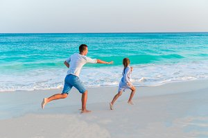 Father with daughter have fun on white tropical beach on caribbean island in sunset light
