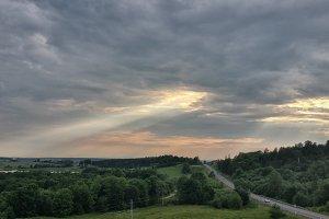 Asphalt road through the tree clouds on sunset sky
