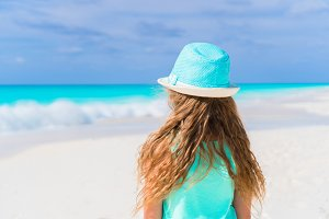 Little girl in hat walking at beach during caribbean vacation