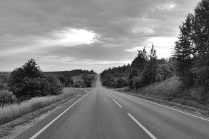 Asphalt road through the tree clouds on sunset sky, black and white