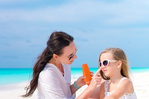 Young mother applying sun cream to daughter nose on the beach. The concept of protection from ultraviolet radiation