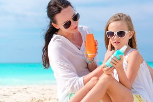 Mom applying sun cream to kid nose on the beach. The concept of protection from ultraviolet radiation