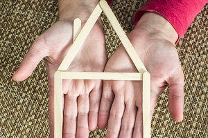 Hands holding model house made of wo