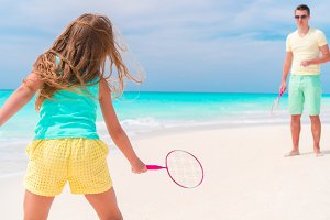 Little girl playing beach tennis on vacation with dad