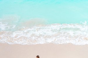 Adorable little girl having a lot of fun in shallow water.View from above of a deserted beach with turquoise water