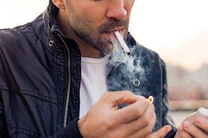Handsome man light his cigarette.