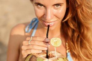 Beautiful girl with coco on beach.