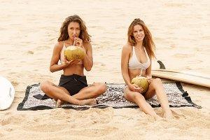 Beautiful girls with coco on beach.