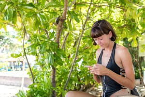 Beautiful woman using smartphone at the beach Nusa Dua of tropical Bali island, Indonesia.