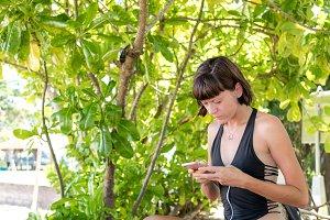 Beautiful woman using smartphone at the beach Nusa Dua of tropical Bali island, Indonesia.