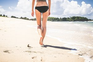 Vacation concept. Close up of female legs walking by the beach of tropical island Bali, Indonesia.