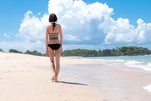 Woman walking on sand beach leaving footprints in the sand. Tropical Bali island, Indonesia.