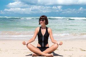 Young beautiful healthy woman making meditation on the beach Nusa Dua, tropical Bali island, Indonesia.