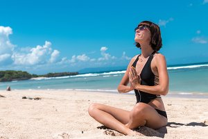 Young healthy attractive woman practicing yoga on the beach Nusa Dua, tropical Bali island, Indonesia. Free space for text.
