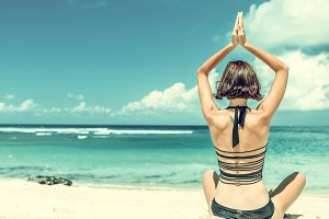 Young healthy attractive woman practicing yoga on the beach Nusa Dua, tropical Bali island, Indonesia.