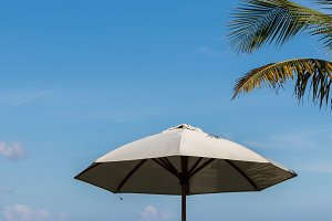 Beach umbrella on a sunny day, sea in background. Tropical beach with black sand. Beautiful sky. Paradise island Bali, Indonesia.