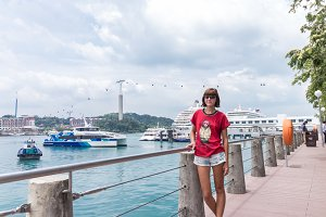 Young woman in Singapore harbor. Cloudy day.