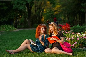 Girlfriends sitting on grass in park