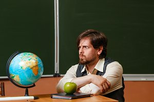 Geography teacher sits
