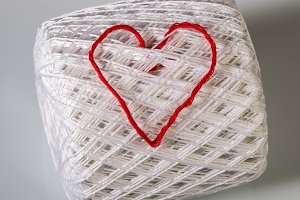 Knitted red heart on white
