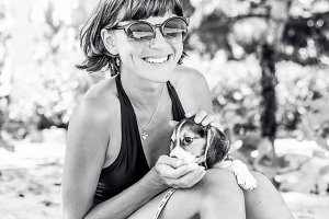 Young attractive girl with her pet dog Beagle at the beach of tropical island Bali, Indonesia. Happy moments. Black and white photo.