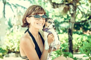 Young attractive girl with her pet dog Beagle at the beach of tropical island Bali, Indonesia. Happy moments.