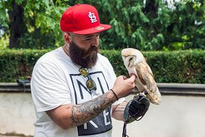 Hipster with an owl in his hand