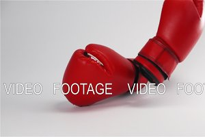 Pair of red leather boxing gloves falling and bouncing isolated on white