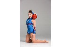 teenager doing gymnastics dance with red gymnastic ball