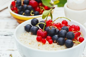 healthy breakfast - oatmeal with fresh berries in a bowl on white, fresh berries on the street