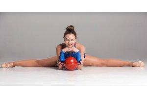 teenager doing gymnastics exercises with red gymnastic ball