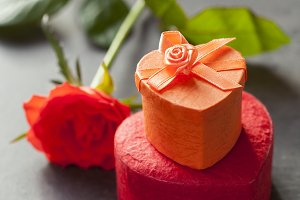 Scarlet red rose and gift boxes in heart shape. Shallow DOF