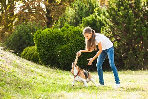 Girl plays with a dog in the yard