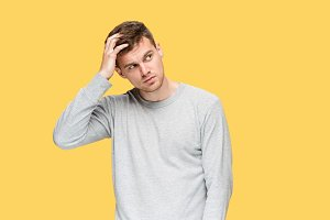 Tired businessman or The serious young man over yellow studio background with headache emotions