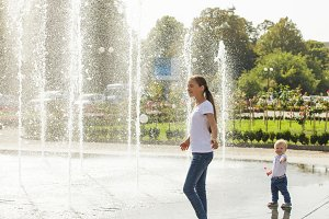 Two happy kids playing in fountain