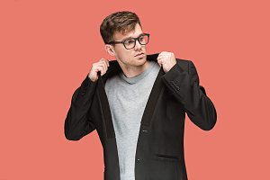 Young handsome man in black suit and glasses isolated on red background