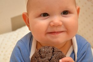 Happy Fancy Beautiful cute baby girl Eating chocolate cookies. Brownies