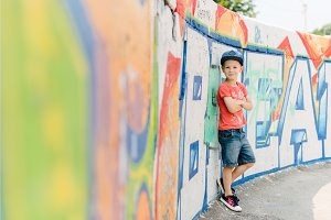 Young happy blond boy leaning on graffiti wall, life style kid